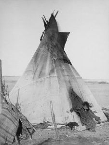 679px-oglala_girl_in_front_of_a_tipi2