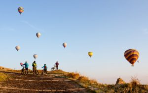 Group of friends with mountain bikes on a trip in the region of Cappadocia, Turkey. In an early morning, as they follow their route, hot air balloons start rising up above them.
